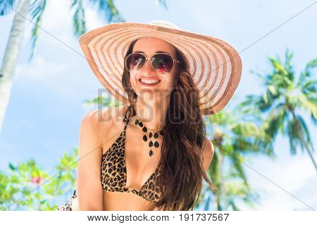 Woman with straw hat at the seaside, smiling in to the camera