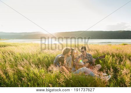 Group of friends in landscape at sundown playing guitar music