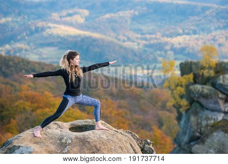 Happy Young Woman Is Practicing Yoga And Doing Asana Virabhadrasana Ii On The Top Of The Mountain. A