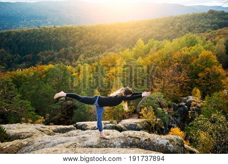 Attractive Fit Female Is Practicing Yoga And Doing Asana Virabhadrasana 3 On The Top Of The Mountain