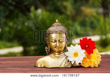 A golden Buddha statue in a summer sunny garden. Buddha and flowers aster. Relax and meditation. Copy space
