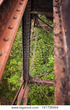 A rusty railway trestle bridge in the middle of the forest.
