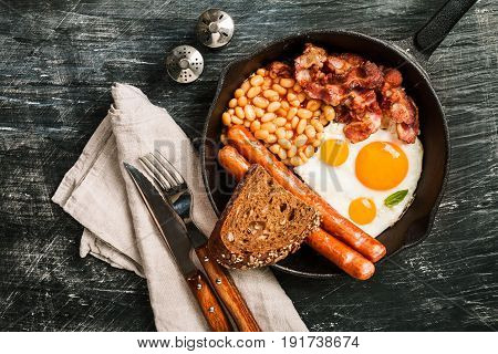 English breakfast - fried egg, beans, tomatoes, sausages, bacon and bread in frying pan over black background. Top view