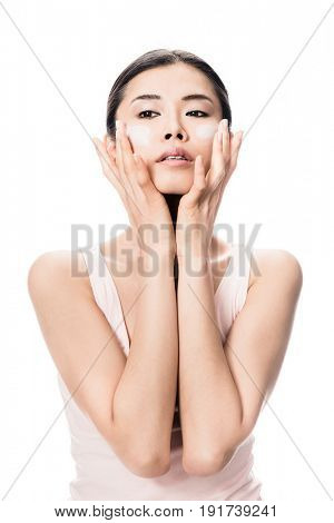 Young woman applying anti-aging soft moisturizer on her cheeks against white background