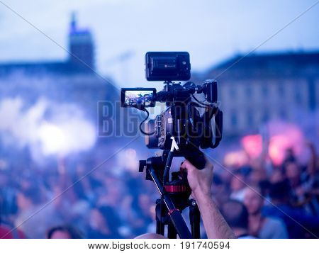 Cameraman broadcasting live event with video camera over the crowd