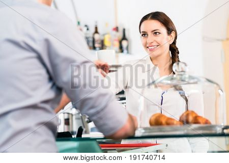 Beautiful waitress serving male customer with a cup of coffee for breakfast indoors