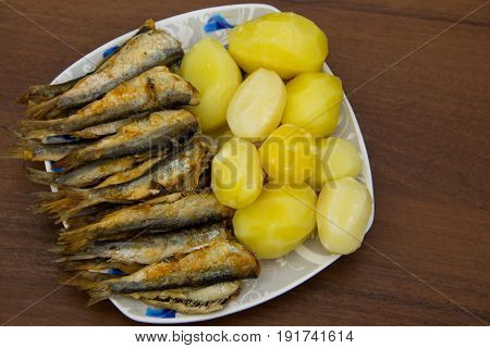 Fried Baltic Herring With Boiled Potatoes On A Plate On Wooden Background