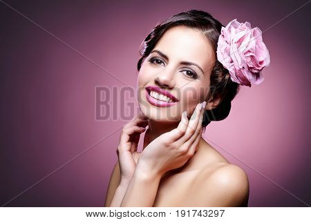 beautiful brunette happy young woman with pink lips and rose in hair. studio beauty shot. copy space.