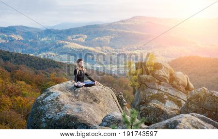 Sporty Young Female Is Practicing Yoga And Doing Asana Siddhasana On The Top Of The Mountain In The