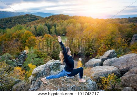 Concentrated Young Female Is Practicing Yoga And Doing Asana Virabhadrasana 1 On The Top Of The Huge