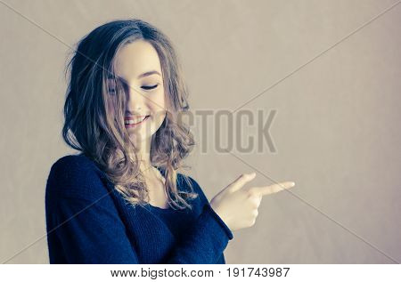 Beautiful smiling teenage girl with curly fair hair pointing to the side. Portrait of hipster woman in black jumper looking down and presenting your product. Emotion facial expression. Copy space.