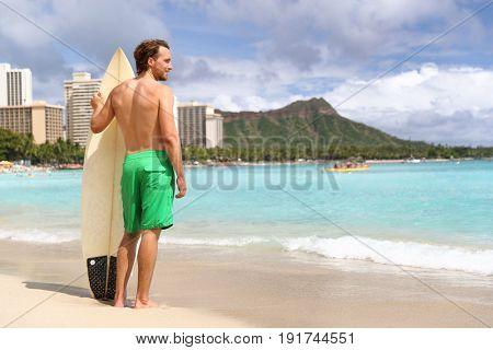 Hawaii surf man surfer surfing on Waikiki beach. Athlete standing with surfboard looking at ocean water, diamond head mountain in the landscape background, hawaiian tourist landmark. Honolulu, Oahu.