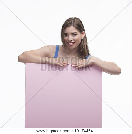 Young happy woman portrait of a confident businesswoman showing presentation, pointing paper placard gray background. Ideal for banners, registration forms, presentation, landings, presenting concept.