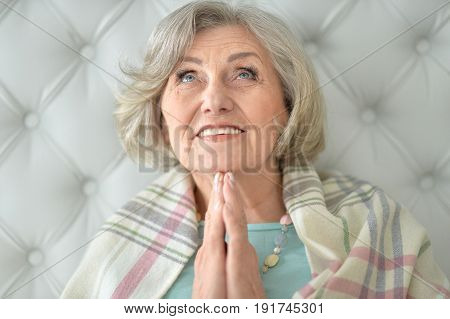 Senior woman sitting on couch and praying