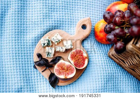 Picnic at the park. Wooden cutting board with two halves of figs basil leaves slices of Dor Blue cheese on blue tablecloth. Picnic basket and peaches on background. Top view