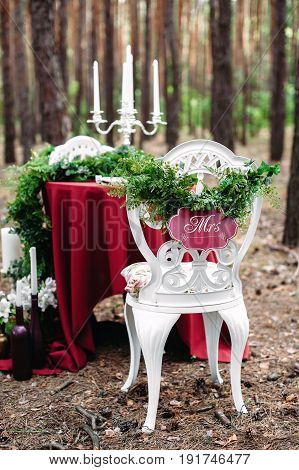 Weeding decor. White forged chair with sigh Mrs. Decorated table served for two in pine forest. Decoration with marsala fabric candles candlesticks wine bottles flowers and grass. Bohemian style.