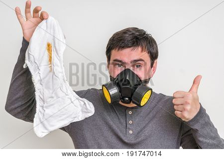 Father with gas mask changing smelly diaper - baby care concept