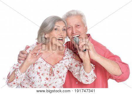 Happy senior couple singing karaoke isolated on white background