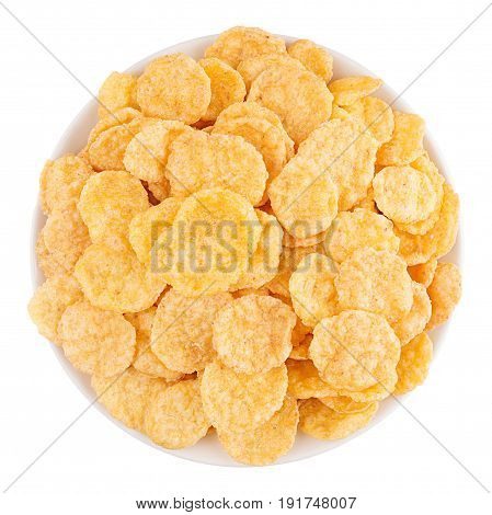 Golden corn flakes in white bowl isolated top view. Cereals.