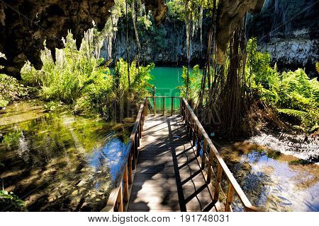 Magnificent view of the mystery misty cave in the jungle with sun rays and wooden bridge in the underground lake. The 3 Eyes National Park (Los Tres Ojos) in Santo Domingo Caribbean Dominican Republic