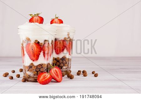 Colorful breakfast with chocolate balls corn flakes sliced strawberry leaves mint in jars on white wood board. Decorative border with copy space.