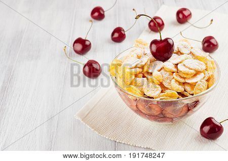 Summer breakfast with golden corn flakes ripe cherries powdered sugar on white wood board. Decorative border with copy space.