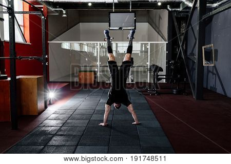 Athlete Walking On His Hands Standing Upside Down In Gym. Man Doing Push Ups On His Hands. Workout L