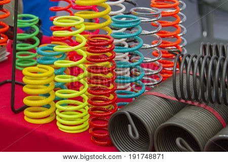 Coil springs are many colors on the red table.