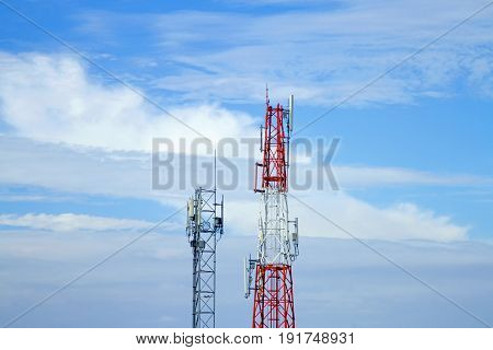 Mobile phone communication tower transmission signal with blue sky background and antenna and twin
