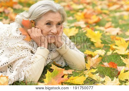 Beautiful senior woman lying on green grass with colorful autumn leaves