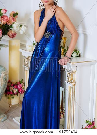Young Beautiful Slim Brunette Girl In Long Blue Dress With Open Shoulders And Decollete Stands With
