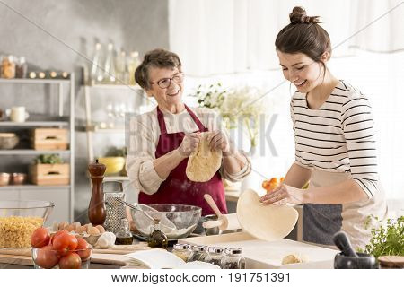 Grandmother preparing traditional pizza with her granddaughter