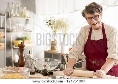 Happy senior woman rolling dough for pizza