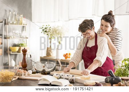Happy grandmother and granddaughter baking cake together