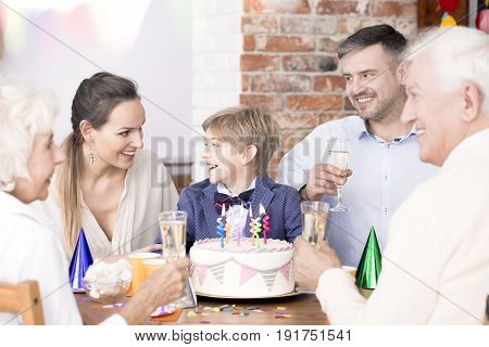 Happy little boy having birthday party with his family