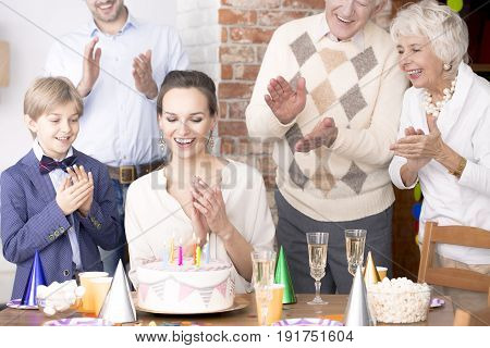 Happy young mom spending birthday with her family at a party