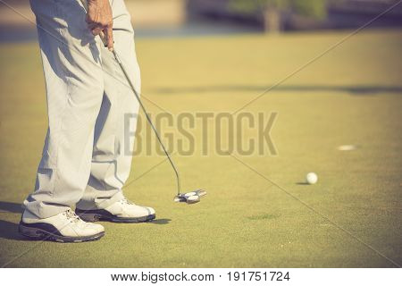 Golf Player At The Putting Green Hitting Ball Into A Hole.vintage Color