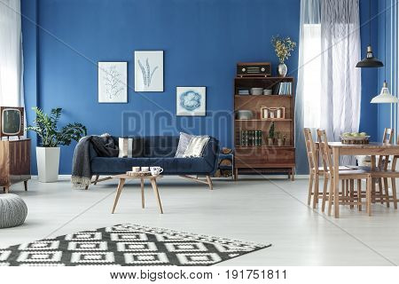 Retro living room with wooden dining table in stylish apartment