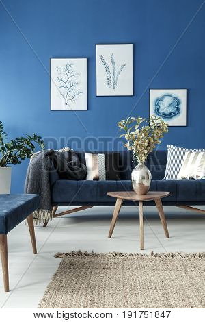 End table with flower vase and retro sofa in blue stylish room