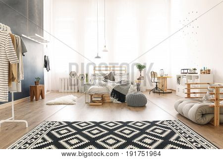 Black and white apartment with DIY pallet bed pattern carpet