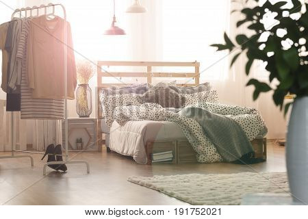 White bedroom with wooden bed lamps window and clothes rack