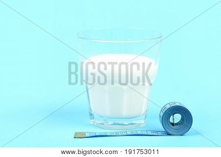 Milk In Glass Near Roll Of Tape For Measuring