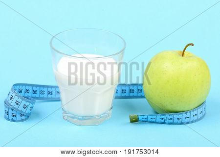 Glass With Milk, Apple And Untwisted Roll Of Measuring Tape