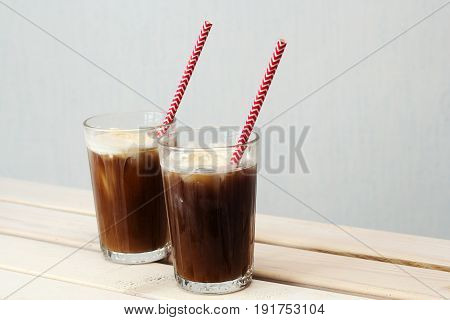 two glasses of cold coffee with ice cream with a cocktail straw on a table against white wall