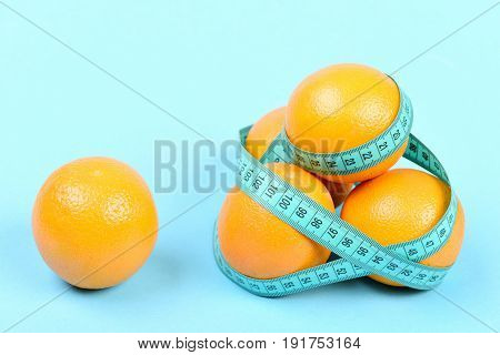 Pile Of Oranges Wrapped Around With Cyan Flexible Ruler
