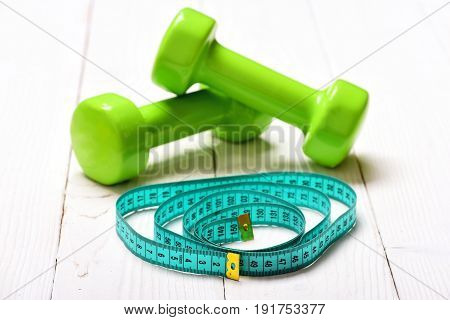 Measuring Tape In Turquoise Colour Circled Near Green Dumbbells