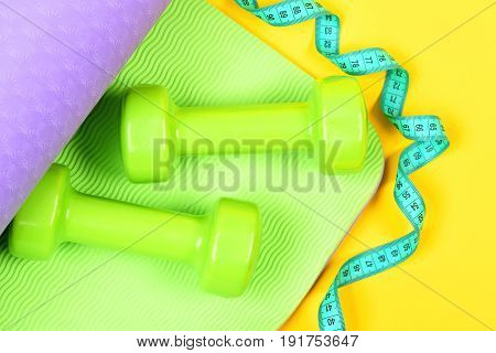 Measuring Tape In Cyan Colour Twisting Around Dumbbells And Mat