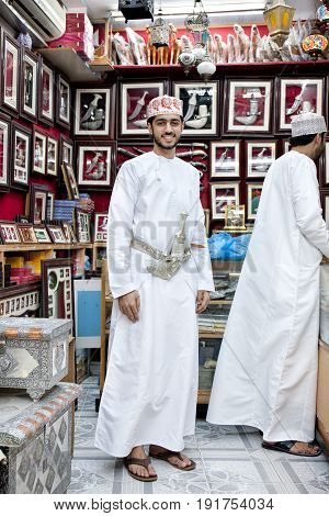MUSCAT OMAN - March 15 2017: An Omani man in a traditional outfit wearing khanjar on Muscat market. A khanjar is a traditional dagger originating from Oman