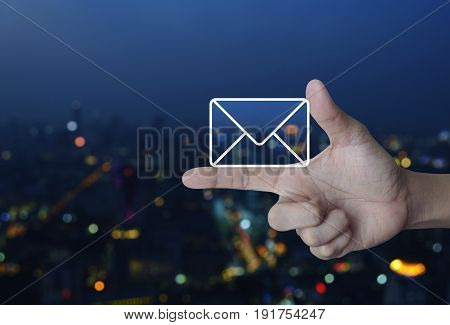 Mail icon on finger over blur colorful night light city tower Contact us concept