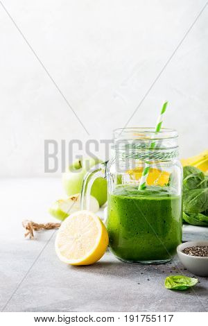 Healthy green smoothie with spinach, banana, lemon, apple and chia seeds in glass jar and ingredients. Detox, diet, healthy, vegetarian food concept with copy space.